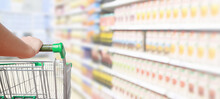 Woman Pushing Shopping Cart With Blur Supermarket Aisle Background
