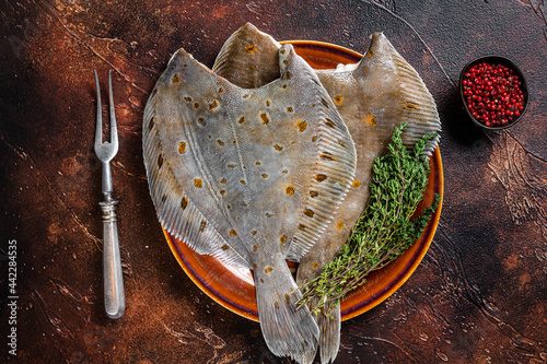 Fototapeta Raw flounder or plaice on rustic plate with herbs