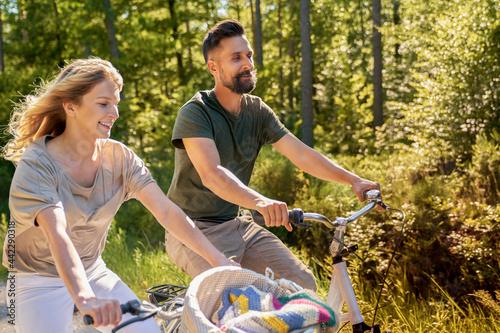 Billede på lærred Happy couple riding bikes in the forest