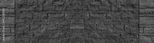 Fotografie, Obraz Black anthracite gray grey  natural  lava basalt stone wall texture, with wild b