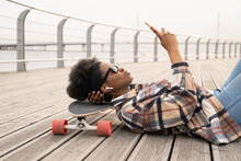 Thoughtful African Woman Texting Hold Smart Phone Serious Pensive Lying On Skateboard On City Quay Or Urban Space. Grumpy Casual Skateboarder Girl With Mobile Phone Messaging Outdoors With Longboard