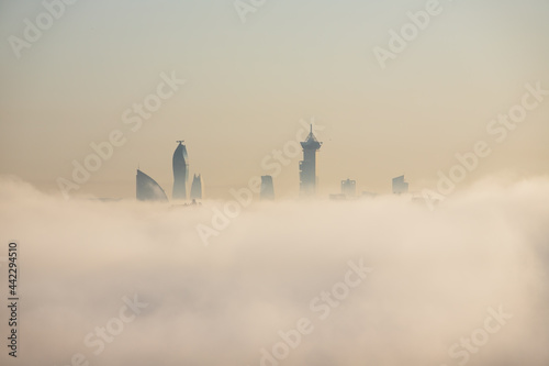 The tops of buildings peek out from the fog Poster Mural XXL