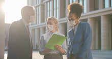 Business Colleagues Wearing Protective Mask Talking Standing Outdoors Near Office Building