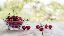 Ripe Sweet Cherries In A Glass Bowl On Wooden Table With Green Bokeh Background, Summer Fruits