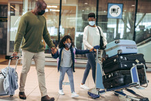 African Family Of Three Walking With Luggage At Airport