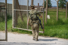 British Army Soldier With SA80 Rifle Guarding A Military Compound Entrance On Salisbury Plain, Wiltshire