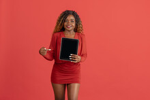 Young Attractive African Girl In Red Short Dress With Tablet In Hands Isolated On Coral Red Background. Human Emotion Concept
