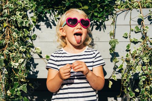 Fototapeta Happy cheerful kid girl in sunglasses having fun shows her tongue