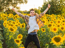 Young Caucasian Man Jumping In A Sunflower Field