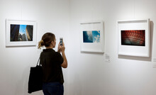 Woman In An Art Exhibition Taking A Photo Of An Art