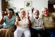 Leinwandbild Motiv Group of cheerful senior friends sitting and watching TV together