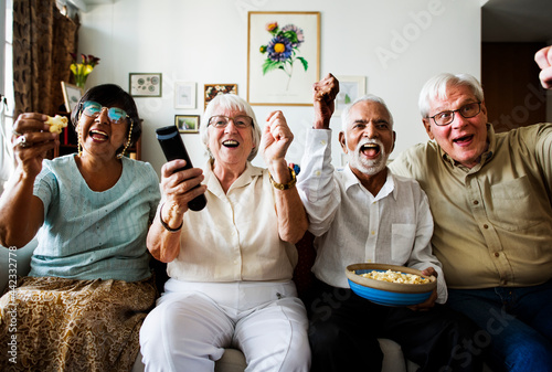 Group of cheerful senior friends sitting and watching TV together Fototapet