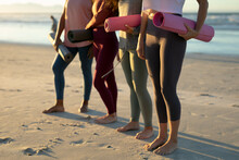 Low Section Of Diverse Female Friends Practicing Yoga, At The Beach Holding Yoga Mats