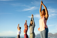Group Of Diverse Female Friends Practicing Yoga, Standing And Rising Hands At The Beach