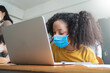 Adorable Black African American girl wearing protective face mask using laptop for studying in classroom at international school.