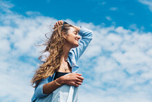 Happy Woman Enjoying Summertime Under Blue Cloudy Sky