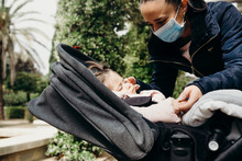 Woman In Mask Taking Care Of Sleeping Baby In Park