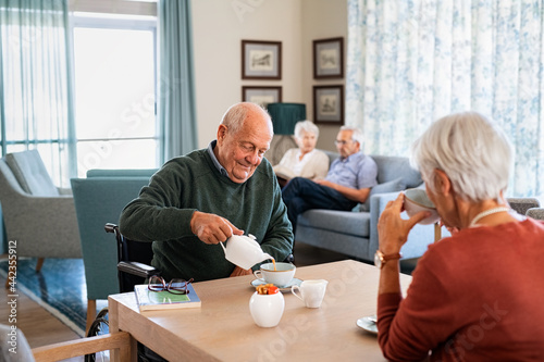 Obraz na plátně Senior man drinking hot tea with his wife at retirement community