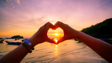 Female Hands In The Form Of Heart  In Sunset Sky At The Sea