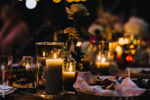 Fotografie, Obraz Candles burning with a flame in a glass candlestick close-up stand on the table at night