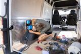 Fototapeta Miasto - Man working on electrical equipment inside a camper van