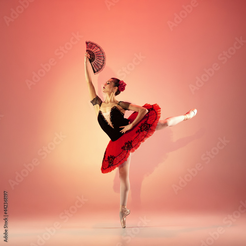 Slika na platnu Young and incredibly beautiful ballerina is posing and dancing at red studio full of light