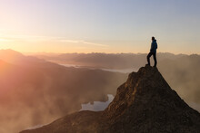 Adventure Composite. Adventurous Adult Man Hiking On Top Of A Mountain. Colorful Sunset Or Sunrise Sky. 3D Rocky Peak. Aerial Background Landscape From Vancouver Island, British Columbia, Canada.