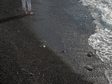 Women's Feet Standing On Shallow Wet Sea Pebbles Near Frothy Water