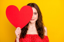 Portrait Of Charming Young Girl Arm Hold Heart Symbol Card Covering One Eye Isolated On Yellow Color Background