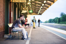 Uni Student Sitting On Bench At Train Station Waiting For Train