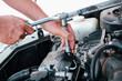 Car repair. Auto mechanic working on car engine in mechanics garage. Repair service. close-up shot