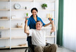 Post-stroke rehabilitation. Female physiotherapist helping elderly male patient in wheelchair to make exercises at home