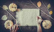 Halloween Grunge Black Background, Pumpkins, Black Spiders, Dry Branches, Orange Leaves Decoration. Autumn Composition Frame, Flat Lay, Vintage Paper, Woman Hand With Pencil, Copy Space.