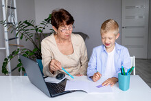 A Teacher Or Grandmother Is Engaged At Home With A Blond Boy On Distance Learning Or A Tutor Is Engaged With A Student At Home, Back To School