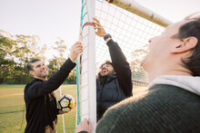 Horizontal Shot Of Three Men Smiling One Holding A Soccer Ball And Two Touching The Net