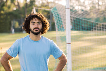 Horizontal Half Body Shot Of A Man With Curly Hair With Arms In The Side With Goal In The Background