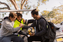 Horizontal Shot Of Men With One Holding A Soccer Ball And Two Shaking Hands All In Casual Clothes