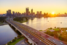 Aerial Of The Sunrise Over The Perth Skyline With Morning Traffic On The Narrows Bridge And River.