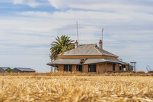 An Old Abandoned Farmhouse Sitting In The Middle Of Paddock