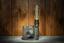 A Lamp Made Of An Old Film Camera On A Wooden Background