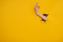 Female Hand Gesture Ok Through A Hole In Yellow Background