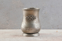 Antique Metal Cup On A Concrete Background.