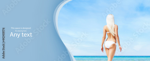 Fotografie, Obraz Beautiful, young and happy blond woman walking on the beach in white swimsuit