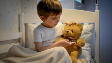 Portrait Of Cute Sick Boy Measuring Temperature To His Toy Teddy Bear With Digital Thermometer. Concept Of Child Virus And Kids Protection During Coronavirus Covid-19 Pandemic.