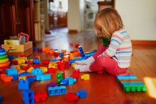 Adorable Little Girl Playing With Colorful Plastic Construction Blocks At Home, In Kindergaten Or Preschool