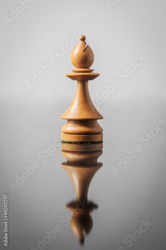 Foto the bishop chess piece on white background with reflection in table