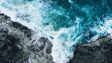 Drone Shot Of Ocean Waves Clashing Into Dark Rocks