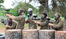 Group Of Young Paintball Players Aiming With Guns In Shootout Outdoors