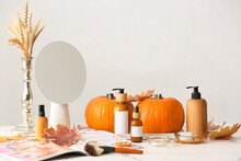 Pumpkins And Bottles Of Cosmetic Products On Light Background