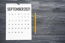 Flip Paper Calendar And Pencil On Dark Wooden Background